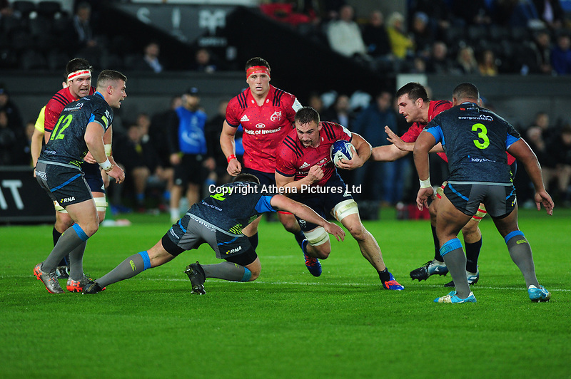 Jack O'Donoghue of Munster is tackled by Scott Otten of Ospreys during the Heineken Champions Cup Round 1 match between the Ospreys and Munster at the Liberty Stadium in Swansea, Wales, UK. Saturday 16th November 2019