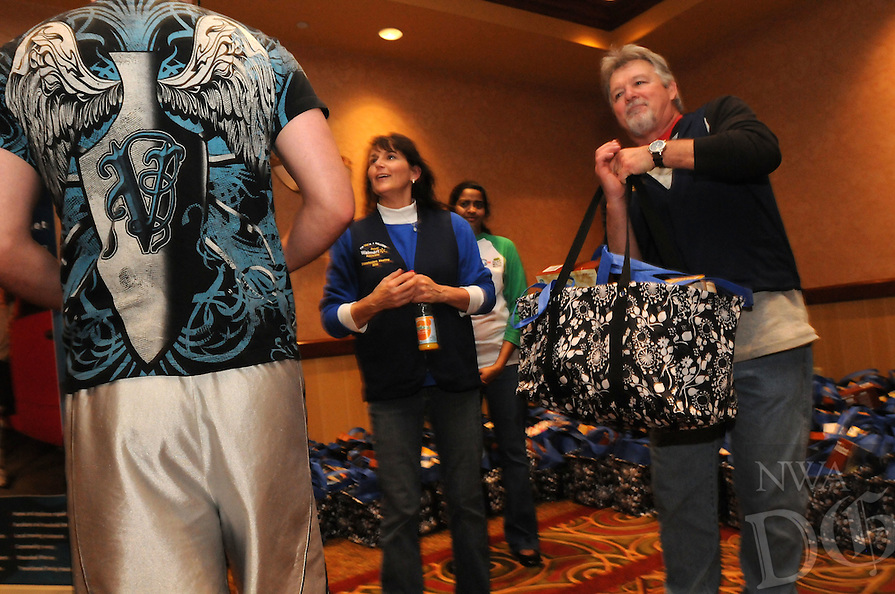 NWA Democrat-Gazette/FLIP PUTTHOFF<br /> Laura Blumenstein greets a veteran Saturday Dec. 12, 2015 while her husband, Bob, hands out bags with all the fingredients for a Christmas dinner. Veterans received the food gifts at Embassy Suites in Rogers, distrubuted by Walmart associates and volunteers.