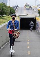 BOGOTA, COLOMBIA - March 13:  A wears a face masks as she rides a scooter on a bike line on March 13, 2020 in Bogota, Colombia. The World Health Organization declared a global pandemic as the coronavirus rapidly spreads across the world. Colombian President Ivan Duque declared a health emergency to contain an outbreak of coronavirus, suspending public events with more than 500 people. (Photo by John W. Vizcaino/VIEWpress via Getty Images)