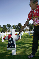 24 April 2004 - Coleville-sur-Mer, France - Mark Emmett reaches out to touch the cross marking the tomb of his uncle Robert L. Emmet - killed in July 1944 - in the American military cemetary of Coleville-sur-Mer, France, 24 April 2004. The American flag, which he brought over from California and wrapped around the cross, was presented to his father by the US Army at Robert's death.