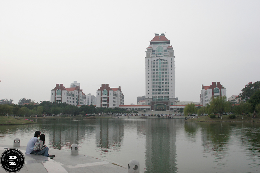 A couple rests near the lake on the grounds of Xiamen University in Xiamen, China.  The university is one of the most prestigious institutions of higher learning in China. Photograph by Douglas ZImmerman