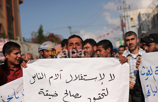 Palestinian supporters of Hamas movement hold banners during a protest organized by the owners of houses which were destroyed by Israeli shelling during the most recent conflict between Israel and Hamas, calling for reconstruction of their destroyed houses in front of the headquarters of the United Nations Relief and Works Agency (UNRWA) in Gaza city, Wednesday, Nov. 5, 2014. Photo by Ashraf Amra