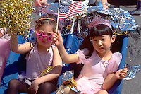 Sisters age 4 with US  flag and plant.  In the Heart of the Beast May Day Festival and Parade Minneapolis  Minnesota USA