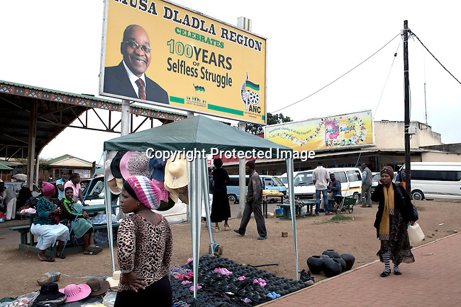 NKANDLA, SOUTH AFRICA - OCTOBER 10: Residents walk past a big billboard celebrating 100 years of selfless struggle on the main road in South African president Jacob Zuma's birth village on October 10, 2012 in KwaNxamalala, Nkandla. South Africa. The South African government is spending R240-million (about US$ 27 million) to construct the vast property for his large family. (Photo by Per-Anders Pettersson)