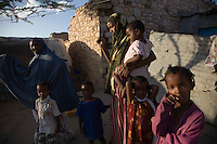 """Koos Aw Dahir - 40, left and Siida Noor Ahmed, right..Has been living in State House since 1992 .11 children - oldest, 22, youngest, 3.Koos looks after four of Siida's children. .Siida fled mogadishu after losing her husband and 3 children to the war. she is staying  now at State House IDP camp, Hargeysa. Somaliland...""""I have 11 children and my own problems, but I was touched by the problems of Siida.  I fled Somaliland during the 1988 war in Somalia so I know the problems of a refugee.  I cannot forget the war.  There was fighting, bullets.  Our men were being slaughtered in front of us like goats.  When we fled, we were afraid of wild animals.  Hyenas are around during war - they like the taste of human flesh.""""  ..""""When people first arrive, they are very afraid. They still have the feeling of where they've come from.  When I look at them, it's like looking at people running out of a burning house.  The new families who come here have nothing so they rely on us.""""  .. """"When it was built, State House was very beautiful.  I never went in and saw it, the closest you could get was the gate.  But people who'd seen inside used to tell stories, it was marvelous.  .There are so many problems here now though.  There is no water, no medical centre, no playgrounds for the children."""".  .""""I want the international community to look with a kind eye on the community living in State House.  Already we are displaced in our own country with no water, education, health services.  At the same time, we have another group of refugees adding to our problems.""""."""