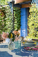 A blue and white tiled garden table is used regularly for al fresco dining