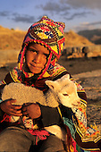 Sachsayhuaman, Peru. Boy in traditional dress holding a young llama 'cria'.