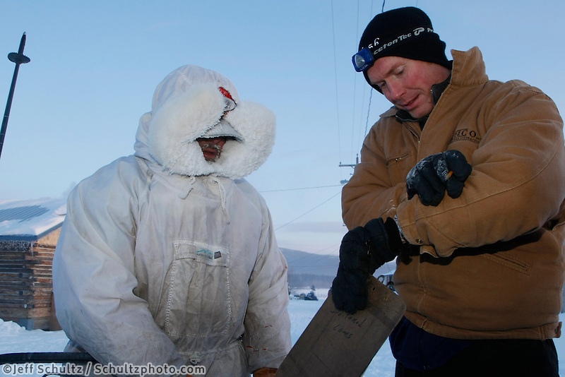 Volunteer comms/checker Jadee Moncur checks in Cim Smyth at Kaltag on a cold 20 degrees below zero  Sunday morning.  Iditarod 2009