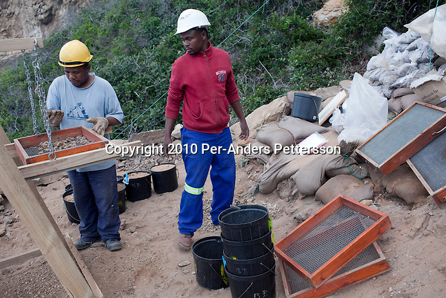 MOSSEL BAY, SOUTH AFRICA - MAY 26:  Unidentified men sort gravel outside a cave called PP13B on May 26, 2010, at Pinnacle Point near Mossel Bay South Africa. The cave sheltered humans between 164,000 and 35,000 years ago, at a time when Homo sapiens was in danger of dying out. These people may have been the ancestors of us. (Photo by Per-Anders Pettersson/Getty Images).