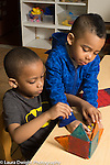 Preschool 3-4 year olds two boys playing together with small plastic figures and colorful magnetic blocks structure