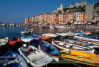 Portovenere, Italy. Overview of city from small boat harbor, with colorful boats at anchor.