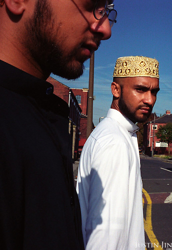 Esmot (in white) and Abdallah walk in their town in Northern England... .Here, a generation of Muslims is growing up separated from the indigenous society. They go to predominantly Asian schools and hang out with Asian friends. Often the only contact between the two communities is through uncertain glances on the street or in local tabloids. Although the atmosphere on the    streets seems friendly, few people dare to step out of their own territory for fear of assault. Stuck in a Western society but feeling unwelcome and without many chances to escape from the ghetto, many youngsters seek identity in Islam. ..Photo by Justin Jin. Northern England, November 2001.