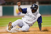 Lastings Milledge #14 of the Charlotte Knights slides across home plate with the tying run in the top of the 9th inning against the Pawtucket Red Sox at McCoy Stadium on June 14, 2011 in Pawtucket, Rhode Island.  The Knights defeated the Red Sox 4-2 in 11 innings.    Photo by Brian Westerholt / Four Seam Images