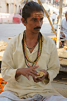 Man assisting Hindu worshipper in their prayer (Puja) at river Ganga by offering Tika and reciting Mantra