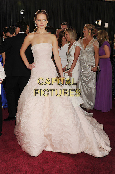 Jennifer Lawrence (wearing Dior Haute Couture).85th Annual Academy Awards held at the Dolby Theatre at Hollywood & Highland Center, Hollywood, California, USA..February 24th, 2013.oscars full length white pale pink strapless dress gown voluminous clutch bag full-tiered skirt hand on hip.CAP/ROT/TM.©Tony Michaels/Roth Stock/Capital Pictures