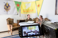 August 2017. YPG Media Centre, Raqqa, Syria.<br /> Foreign volunteer fighters 'Macer Gifford' (left) and 'Zîlan' (right) both from the UK broadcast their reaction to a BBC article stating that any foreign volunteer fighting for the YPG (the Kurdish militia in Syria of which they are part of) are risks to the UK's national security at the YPG Media Centre.<br /> The MFS (Syriac Military Council) are a group of Assyrian Christians who fight alongside the Syrian Democratic Forces in the fight to topple ISIS.<br /> Photographer: Rick Findler