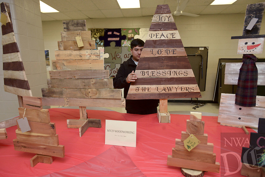 NWA Democrat-Gazette/BEN GOFF @NWABENGOFF<br /> Denis Flores, a Crossroads sophomore, arranges a Christmas tree decoration made from reused palet wood on Monday Dec. 19, 2016 during the Project 479 Christmas Bazaar at the Crossroads alternative education campus in Rogers. The school holds the bazarr, as well as one in the spring, to allow high school students to showcase their creativity by making and selling crafts. Flores and three other students partnered under the name MTCD Woodworking to make the decorations with tools available at the school.