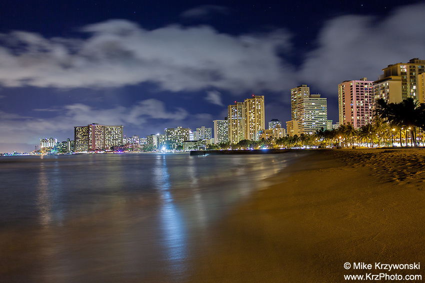 Hotels with lights reflecting off the water at night at Queen's Beach in Waikiki, Oahu