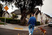 """Ventura, California, July 21, 2010 - Gary Seymour walks with his Staffordshire terrier, Buddy, in their neighborhood. Mr. Seymour says that he walks with Buddy several times each day. """"We get up at six and go to the coffee shop and take a walk up in the hills. In the evenings I walking him over to the Mission [downtown]."""" Mr. Seymour has been homeless off and on for the last thirty years. He currently lives in a camper parked left to him by his father that is parked in the driveway of a friend's mother. Because it is an illegal camp, Mr. Seymour is considered homeless. He says, """"I work odd jobs, landscaping and whatnot to make a little money. I am trying to get back on my feet."""" Mr. Seymour is proud that he does not panhandle. """"I earn my own living without asking people for handouts."""" .."""