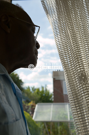 Older man looking out of the window through a curtain,