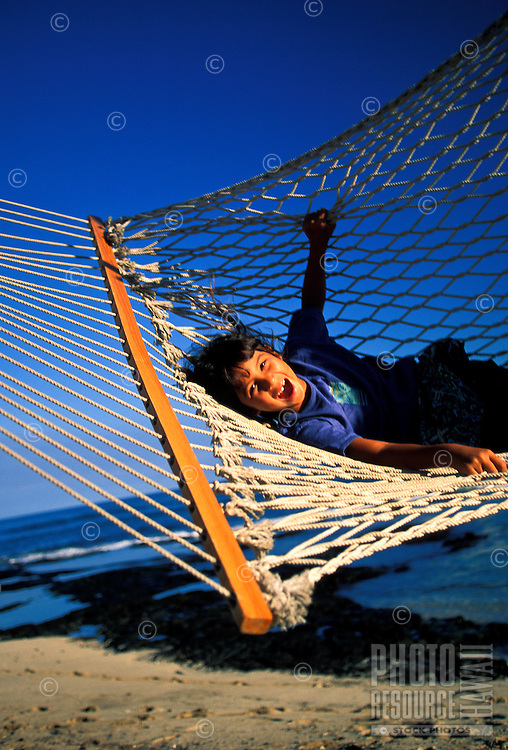 Young girl relaxing in a hammock on the beach