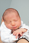 3 day old newborn baby boy asleep held upright closeup