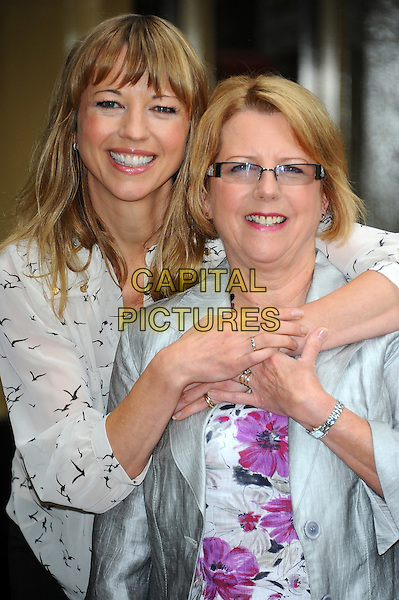 DJ Sara Cox & Jackie Williams.At The Waldorf Hilton Hotel to launch the nominations for the seventh Tesco Mum of the Year Awards, London, England..August 16th, 2011.half length mother mom daughter family white black sheer floral bird print glasses blazer silver hug embrace .CAP/CJ.©Chris Joseph/Capital Pictures.