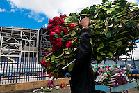 A Colombian man carries roses in the flower market of Bogota, Colombia, 10 July 2010. Colombia is one of the world leaders in cut flower industry. The advantage of the moderate sunny climate, very cheap labor force in combination with the absence of social laws and environmental regulations have created perfect conditions for the cut flower production. Flower growing is very fragile and necessarily depends on irrigation and chemical maintenance, provided by highly toxic pesticides. About 110.000 workers in Colombia, working mainly for living minimum wage, keep the floral industry going and saturate the market generated by consumerist culture the US, Canada and Europe.