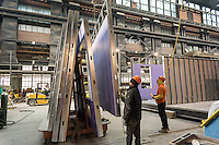 Workers maneuver a wall in place for modular housing in the Capsys factory in the Brooklyn Navy Yard in New York on Thursday, February 11, 2016. Because of rising rents and the need for a specialized space the factory will be closing down after after this job, housing for the Nehemiah Spring Creek development. Steiner Studios, another tenant at the Brooklyn Navy Yard will be taking over the space. (© Richard B. Levine)