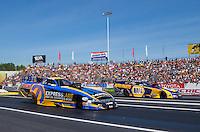 Jun 7, 2015; Englishtown, NJ, USA; NHRA funny car driver Matt Hagan (left) races alongside teammate Ron Capps during the Summernationals at Old Bridge Township Raceway Park. Mandatory Credit: Mark J. Rebilas-