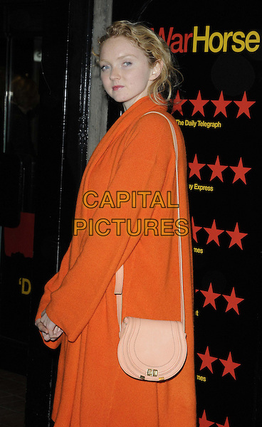 Lily Cole.The 5th anniversary performance of 'War Horse' at The New London Theatre, Drury Lane, London, England..October 25th, 2012.half length orange cardigan pink bag purse side .CAP/CAN.©Can Nguyen/Capital Pictures.