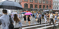 Pedestrians break out their umbrellas or run between the rain drops during a shower in the Chelsea neighborhood of New York on Tuesday, July 14, 2015. Scattered showers with a high in the 80's F, typical muggy New York summer weather, are expected today. (© Richard B. Levine)