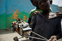 A young Haitian boy shows a home made armoured vehicle toy on the street of the slum of Cité Soleil, Port-au-Prince, Haiti, 24 July 2008. Cité Soleil is considered one of the worst slums in the Americas, most of its 300.000 residents live in extreme poverty. Children and single mothers predominate in the population. Social and living conditions in the slum are a human tragedy. There is no running water, no sewers and no electricity. Public services virtually do not exist - there are no stores, no hospitals or schools, no urban infrastructure. In spite of this fact, a rent must be payed even in all shacks made from rusty metal sheets. Infectious diseases are widely spread as garbage disposal does not exist in Cité Soleil. Violence is common, armed gangs operate throughout the slum.