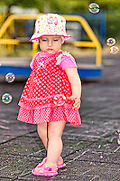 A pretty little girl with white hat having fun with bubbles