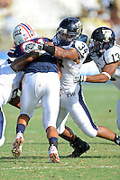 30 October 2010:  FIU linebacker Winston Fraser (34) tackles Florida Atlantic tight end Rob Housler (81) in the first quarter as the Florida Atlantic University Owls defeated the FIU Golden Panthers, 21-9, at Lockhart Stadium in Fort Lauderdale, Florida.