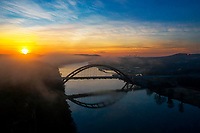 Aerial view of a colorful sunrise and foggy lake greets the 360 Bridge over Lake Austin. This is my favorite Austin landmarks to shoot.
