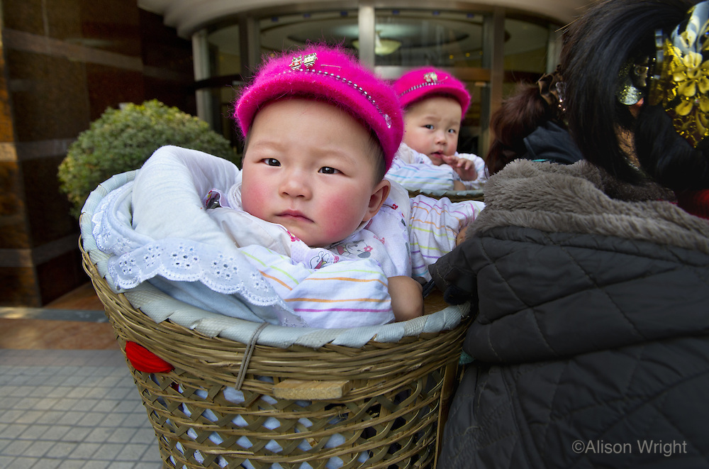 Baby twins being carried in baskets on their aunts backs.
