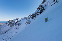 Female climber climbing steep snowy couloir on winter ascent of Mannen mountain peak, Moskenesøy, Lofoten Islands, Norway