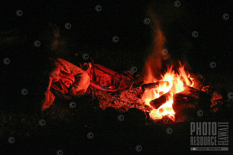 A portrait of a young woman relaxing near an evening fire in Hawai'i.
