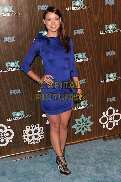 OLIVIA WILDE.Fox Winter All Star  Party held at Villa Sorisso, Pasadena, California, USA..January 11th, 2009.full length blue purple dress long sleeves hand on hip black clutch bag strappy sandals .CAP/ADM/TC.©T. Conrad/AdMedia/Capital Pictures.