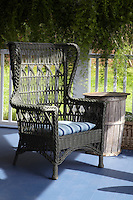 Close up of a high back wicker chair on the porch of James Huniford's home