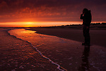 Sunset at Walberswick beach in Suffolk England with a young teenage girl standing alone