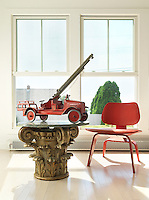 Detail of a small red Eames chair and a vintage toy fire-engine on a table in the style of a Corinthian column