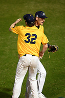 Pitcher Justin Butera (21) of the Merrimack Warriors gets a hug from starting pitcher Cedric Gillette (32) after earning a save in a game against the Michigan State Spartans on Saturday, February 22, 2020, at Fluor Field at the West End in Greenville, South Carolina. Merrimack won, 7-5. (Tom Priddy/Four Seam Images)