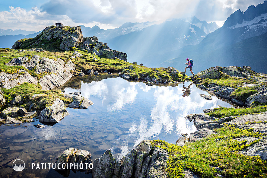 Hiking the trails along the edge of the Aletschgletscher, the Alp's largest glacier, from Bettmeralp and Riederalp, Switzerland. A hiker walks the edge of a small pond as God's rays and sun beams stream through the sky