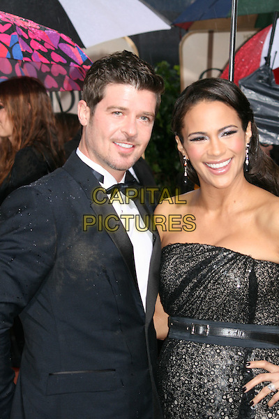 ROBIN THICKE & PAULA PATTON .Arrivals at the 67th Golden Globe Awards, he Beverly Hilton Hotel, Beverly Hills, California, USA, .January 17th, 2010..globes  Half length couple married couple husband wife  black strapless dress bow tie tux tuxedo waist belt smiling .CAP/AW/MAZ .©Maz/Weber/Capital Pictures.