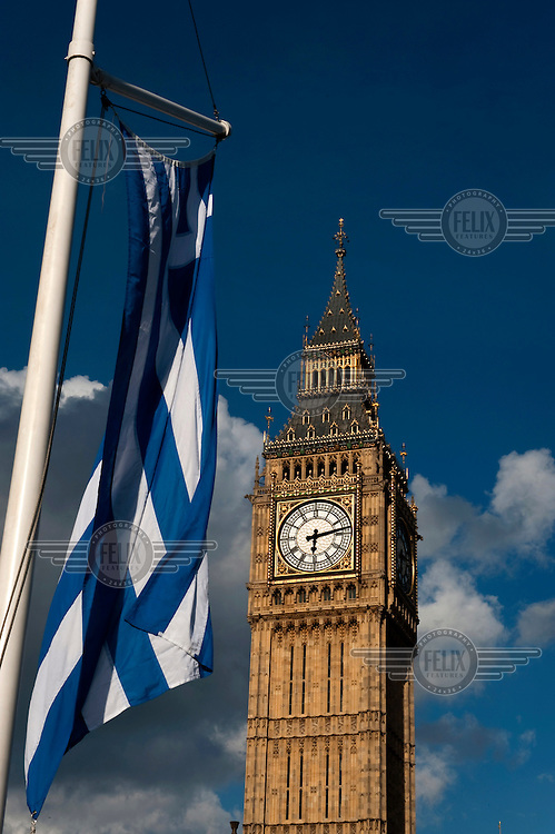 A Greek flag flies in front of The Clock Tower at the House of Commons in Westminster, London. Although the tower is popularly referred to as Big Ben, this is actually the nickname of the bell housed within whose official name is the Great Bell.