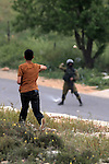 A Palestinian protester throws stones towards a member of Israeli security forces during clashes following a protest marking the Palestinian Land Day in the West Bank village of Nabi Saleh near Ramallah, March 28, 2015. Land Day commemorates the unrest that erupted in March 1976 when Israeli Arabs protested the Israeli government's confiscation of thousands of acres of Arab-owned land and in which six Arab citizens were killed by Israeli police. Photo by Shadi Hatem