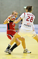 22 MAR 2012 - LOUGHBOROUGH, GBR - Great Britain's Nina Heglund (GBR) (left, in red and blue) looks for a way past Poland's Alina Wojtas (POL) (#28, in white and red) during the women's 2012 European Handball Championships qualification match at Loughborough University in Loughborough, Great Britain .(PHOTO (C) 2012 NIGEL FARROW)