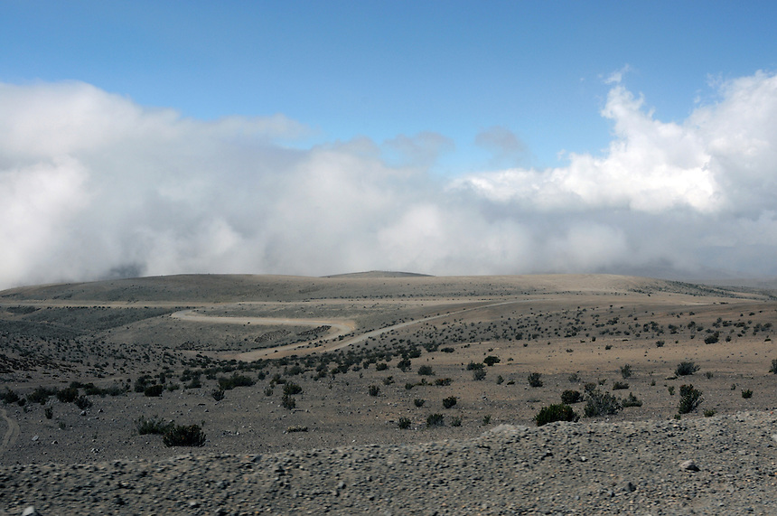 Bleak and desolate 'paramo' ecosystem on approach to Mt. Chimborazo. Though seemingly flat it is 4000 meters (4 km) above sea level, as evidenced by the clouds on the horizon.
